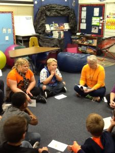 Lucy reading ghost station chapter to students
